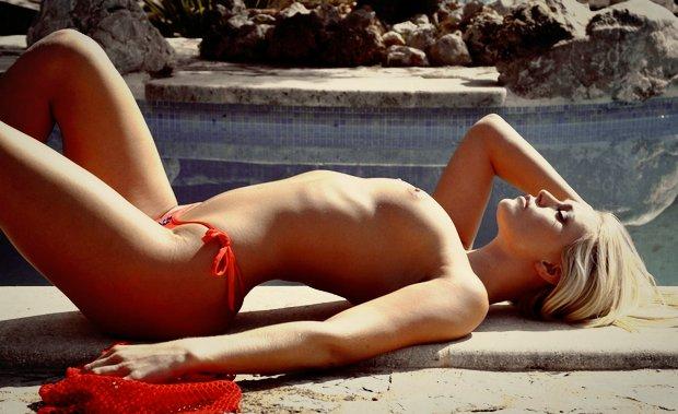Une jeune et belle blonde nue se repose sous les rayons du soleil